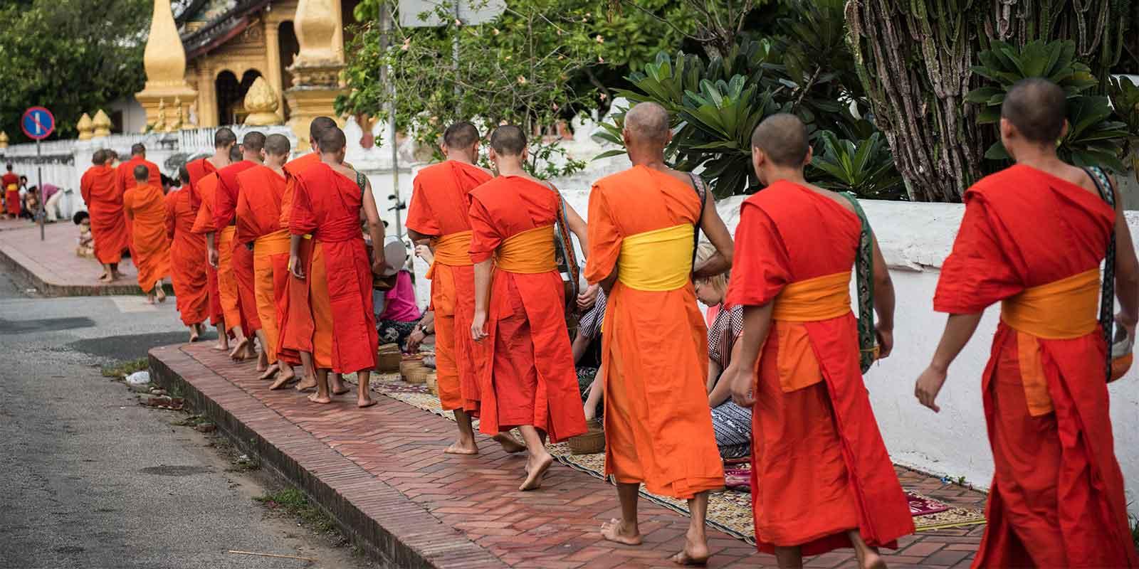 Buddhist monks walking outside temple in Laos
