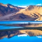 Trekkers enjoying the scenery and reflection of Pagong Tso Lake in Ladakh, India