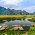 Traditional boats on the lake, with picturesque mountain scenery in th background, at Van Long Nature Reserve in Vietnam