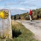 Hiker passing sign of Camino de Santiago