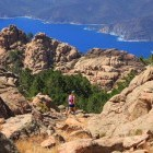 Hiker walking through mountains with sea in the distance on the island of Corsica