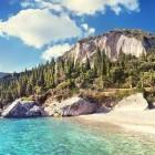 Sandy beach and turquoise sea of Corfu alongside mountain scenery
