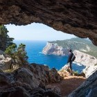 Hiker looking at seaview from cave in Sardinia