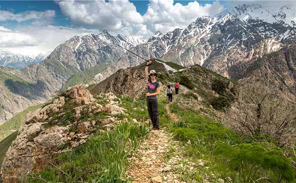 Hiker waving her trekking pole in the Chimgan Mountains of Uzbekistan