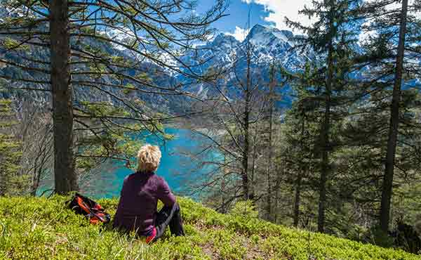 Hiker resting in Austria Alps overlooking lake