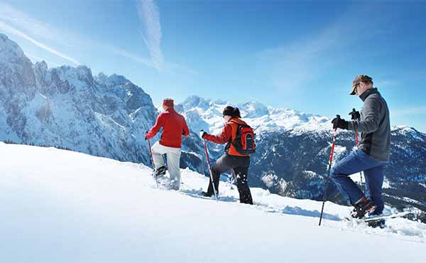 Small group of hikers snowshoeing in Austrian Alps in winter